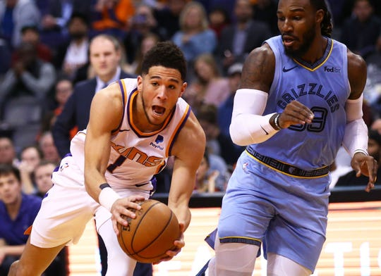 Phoenix Suns guard Devin Booker (1) drives into the lane against Memphis Grizzlies forward Jae Crowder (99) in the first half on Dec. 11, 2019 in Phoenix, Ariz.