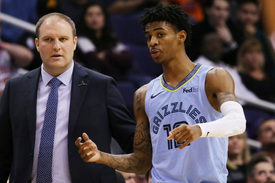 Memphis Grizzlies guard Ja Morant, right, talks with head coach Taylor Jenkins during the second half of an NBA basketball game against the Phoenix Suns, Wednesday, Dec. 11, 2019, in Phoenix. The Grizzlies defeated the Suns 115-108. (AP Photo/Ross D. Franklin)