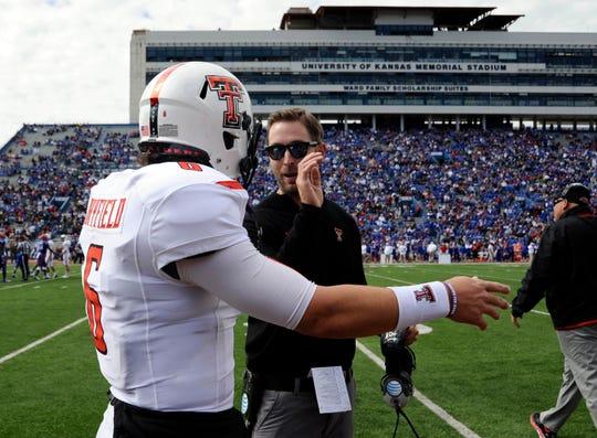 Texas Tech coach Kliff Kingsbury talks to quarterback Baker Mayfield after a touchdown against Kansas on Oct 5, 2013.