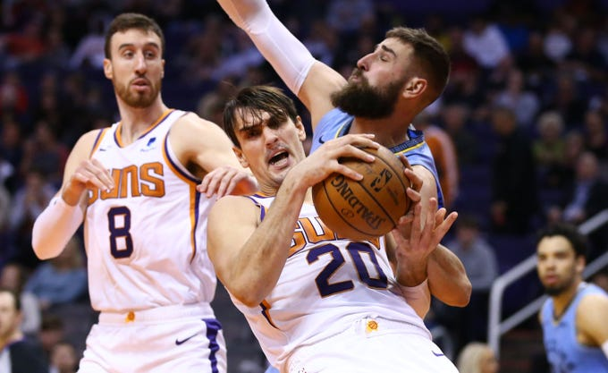 Phoenix Suns forward Dario Saric (20) battle for the rebound with Memphis Grizzlies center Jonas Valanciunas (17) in the second half on Dec. 11, 2019 in Phoenix, Ariz.