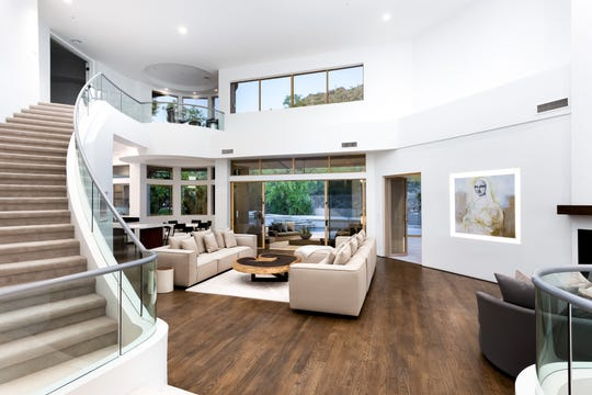 The $2.35M estate, sold by Lee Laris, features a staircase with glass railings.