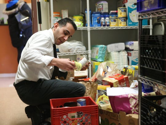 Dutchess Outreach volunteer Sherwin Shirinpour sorts through donations at the Beverley Closs Memorial Food Pantry in the City of Poughkeepsie on December 12, 2019.
