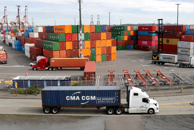 FILE - In this Oct. 2, 2019, file photo trucks hauling shipping containers drive near containers stacked five-high at a terminal on Harbor Island in Seattle. Defying fears and predictions, the American job market is still shrugging off President Donald Trump's trade wars. Employers added an impressive 266,000 jobs in November, and unemployment returned to a 50-year low 3.5% _ all at a time when the Trump administration is engaged in a bruising trade war with China while fighting other U.S. trading partners as well.(AP Photo/Elaine Thompson, File)