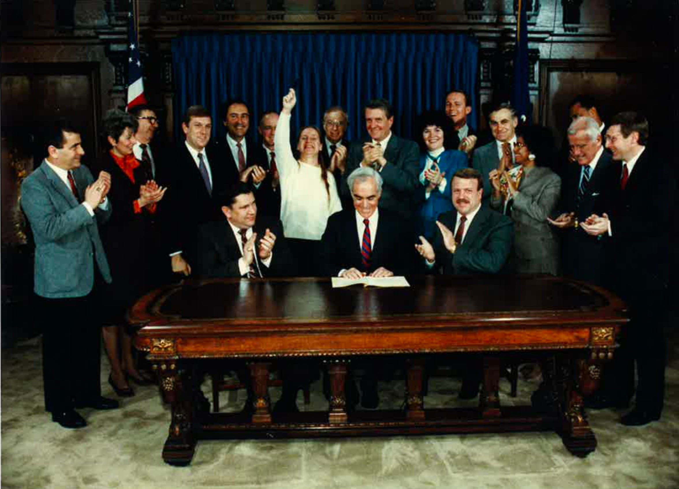 Deb Beck, center back, celebrates as Gov. Bob Casey Sr., center front, signed Act 152 into law in 1988. The law required public insurance to cover drug and alcohol addiction treatment, an expansion of a previous law championed by Beck.