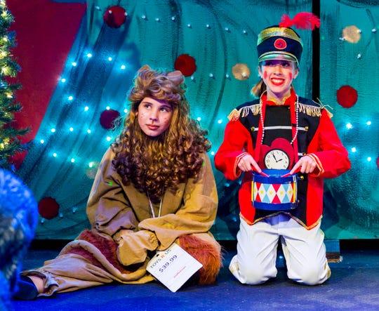 Laurne Joyner, as Stuffed Lion, and Ella Kilgore, as Tin Soldier, sit beneath the tree on Christmas morning.