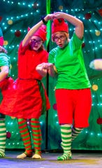 Elves Bailey White, as Curly #1, and Lilly Andersen, as Curly #2, dance together after meeting Dorothy and Toto.