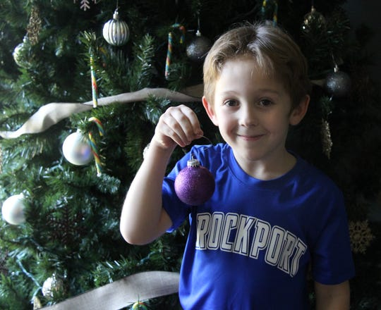 Kale Kakish, 7, of Sweden with one of the 132 ornaments he has made in memory of his late teacher Carrie Ray.