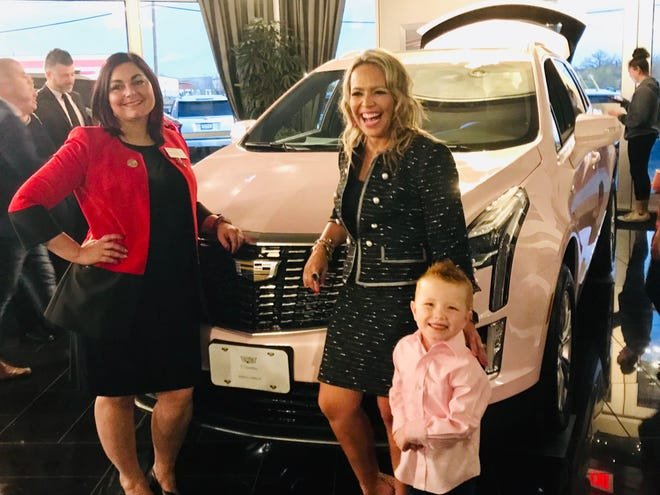 Stacy Emerson (right) stands next to her son and Angela Casavant (left) in front of a pink 2020 Cadillac XT5 Emerson earned as a sales director for Mary Kay Cosmetics. Emerson will lease the vehicle for the next 1-2 years as part of a sales achiever program.