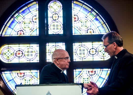 Bishop Paul Swain shakes hands with Bishop-elect Donald DeGrood during a press conference on Thursday, Dec. 12, 2019 at the Catholic Pastoral Center.