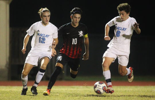 Maclay junior Drew Daunt reaches a ball before Leon senior Henry Regalado and Maclay junior Cade Smith as Maclay pulled out a 1-0 road victory over Leon on Dec. 10, 2019.