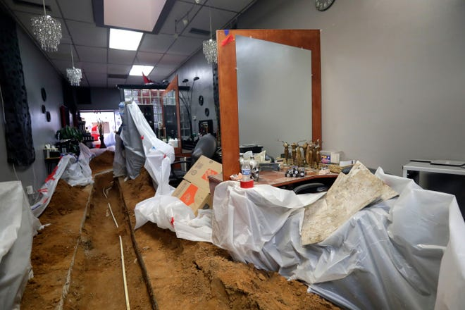 Sewage pipes are exposed in Randazzles Hair Company, located on West College Avenue, and dirt is piled on what remains of the flooring in the hair studio. The sewage line to the salon was cut during construction at a neighboring business.