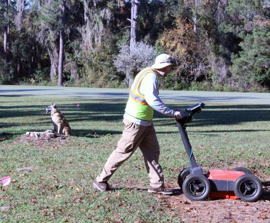 A cadaver dog alerts to the possibility of human remains below the ground as Andrew McFeaters, a National Park Service archaeological technician, runs ground penetrating radar over a suspected burial ground near the 7th hole of the Capital City Country Club.