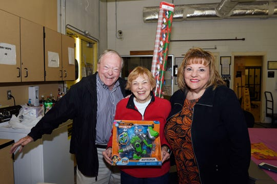 Rotary Club of Port St. Lucie members Charlie and Connie Cox with Catherine Griffin at Treasure Coast High School for the Christmas gift wrapping party.