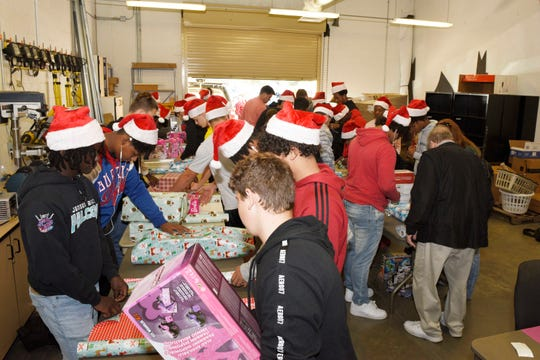 Treasure Coast High School football players wrap Christmas gits for the Rotary Club of Port St. Lucie at the school.