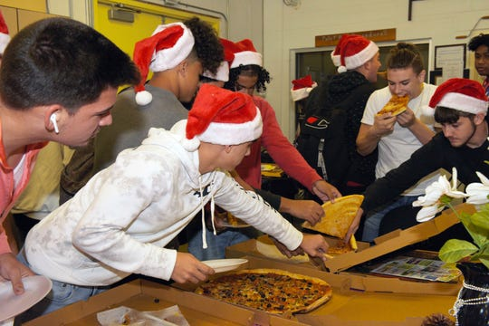 Treasure Coast High School football players are treated to pizza after helping Rotary Club of Port St. Lucie members wrap Christmas gifts for underserved children in St. Lucie County.