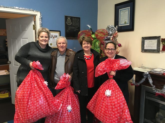 "(From left) Aubrie Bonestell, case manager, Salvation Army Vineland Corps., Michael and Fran Capizola, from the law firm of Capizola, Pancari, Lapham & Fralinger in Vineland, and Major Jacqueline Rivera of the Salvation Army Vineland Corps., were in attendance as the law firm's ""Adopt-a-Family""/""Adopt-a-Child"" donations were presented to the Salvation Army."