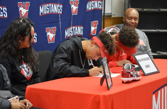 Tulare Western's Elijah Burrell, in black, and his twin brother, Jordan, sign to officially extend their football careers at Davidson College on Dec. 11, 2019 on the Mustangs' campus.