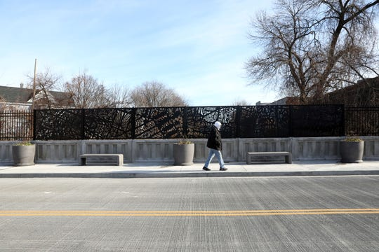 "A pedestrian walks along the 14th Avenue bridge, which features Frances Gallardo's ""Line to Line"" in Mount Vernon, on  Dec. 12, 2019."