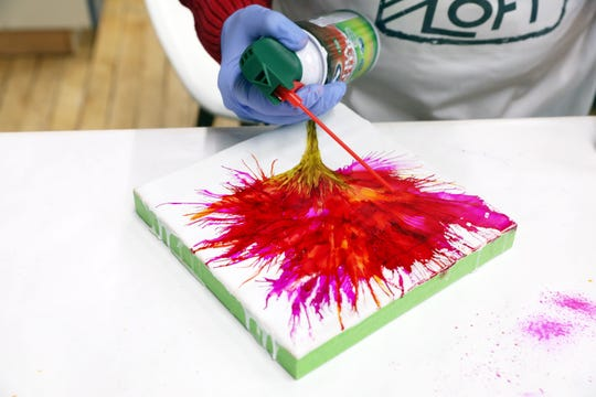 Linda Graham uses canned air to blow alcohol ink on a waxed board at her studio space at The Art Loft in downtown Zanesville.