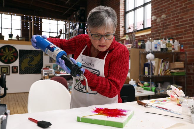 Zanesville artist Linda Graham uses a blowtorch to heat the wax she uses to create her pieces in The Art Loft in downtown Zanesville.