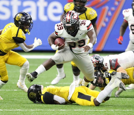 Many running back Shamarion Wiseman (39) jumps over a Ferriday defender during the LHSAA Class 2A football state championship game at the Mercedes-Benz Superdome in New Orleans on Friday, December 13, 2019.
