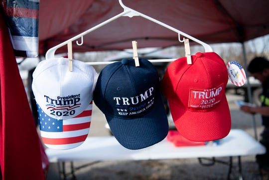 """Traveling vendors sell Donald Trump merchandise on Friday, Dec. 13, 2019 on Dickman Rd. in Battle Creek, Mich. Donald Trump is hosting a """"Merry Christmas"""" rally Dec. 18 at the Kellogg Arena on McCamly Square."""