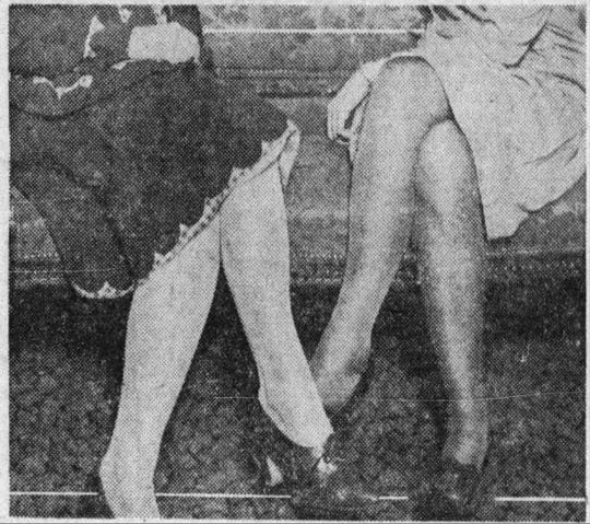 Two women show off the length of their skirts in December 1929.