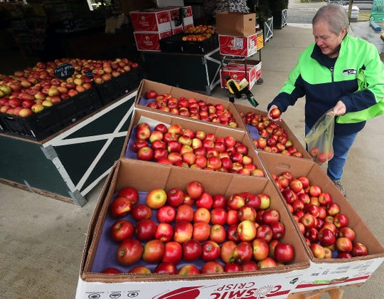 Sandy Heinzle, of Port Orchard, grabs a bag of cosmic crisp apples at Colello's Farm Stand Produce in South Kitsap on Friday. This was the third time Heinzle has stopped by the stand to purchase the apples.