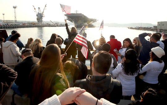 2017 FILE ARTFlags are waved as the USS Nimitz pulls into the pier at Naval Base Kitsap-Bremerton in Bremerton, Washington on Sunday, December 10, 2017. The aircraft carrier and crew returned to its homeport after a 6-month deployment to the Pacific and Indian oceans.