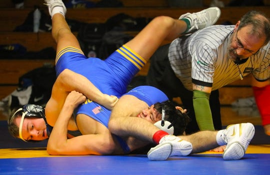 Olympic's Taylor Andrews looks to pin Bremerton's Aiden Harvey during Thursday's wrestling match at Bremerton High School. The Knights beat the Trojans 39-33.