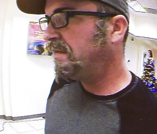 Melbourne police say this unidentified man glued tufts of fake hair to his face while robbing a SunTrust bank.