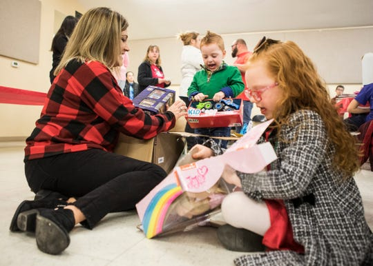 Jaxson Baker-Kuhn and his sister Natalie Baker-Kuhn unwrap presents in front of their soon to be adoptive mom Erin Crabtree during a Christmas party and gift giveaway at the Ross County Fairgrounds where presents where handed out to various foster kids from different counties in Ohio on Dec. 12, 2019.