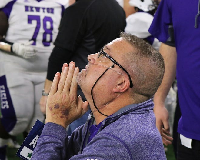 Late football coach W.T Johnston prays on the sidelines during the 2018 Texas 3A division 2 title game.