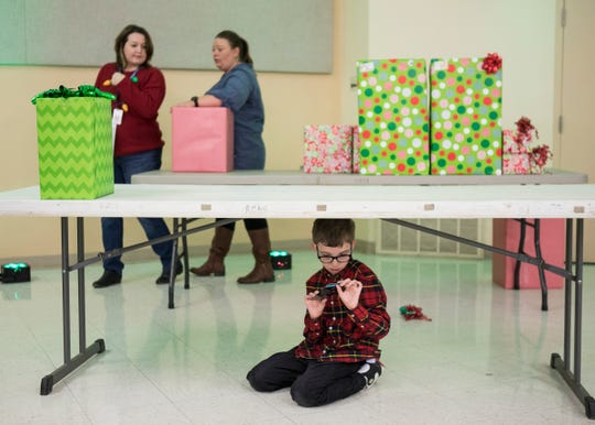 Isaiah Crabtree plays under the table as presents for various foster children were handed out at the Ross County Fairgrounds on Dec. 12, 2019.