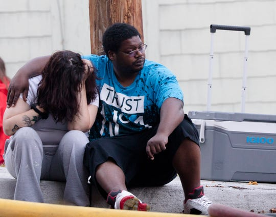 Ivan Tolbert puts an arm around his wife, Arlenia, as Cincinnati firefighters work the scene of a fire that burned multiple buildings on Halstead and Addison streets, including their rented home, on Sept. 23, 2019.