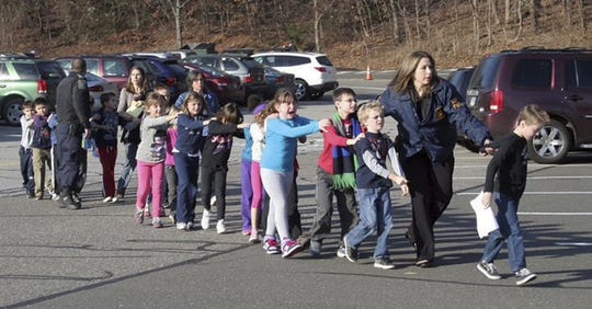 Connecticut State Police lead children quickly away from Sandy Hook Elementary School in a single-file line after the shooting there Friday, Dec. 14, 2012.