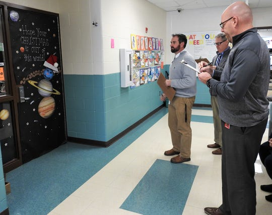 Judges Scott Loomis, Tim Jones and Grant Fauver of Coshocton High School make notes for an entry in the holiday door decorating contest at Coshocton Elementary School. Categories were for best school spirit, winter or holiday theme, originality, neatness and overall best in show.