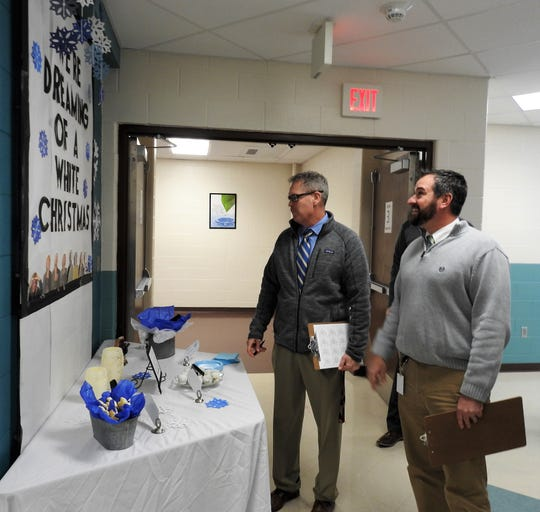 Judges Tim Jones and Scott Loomis review a Christmas display with treats at the entrance of sixth grade at Coshocton Elementary School. It was the second year for the contest designed to foster Christmas spirit and a positive culture in the building among students and teachers.