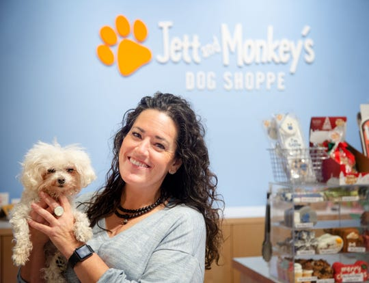 Jennifer Brooks, an owner of Jett and Monkey's Dog Shoppe holds her dog Monkey at her store in the East Village Friday, Dec. 13, 2019.