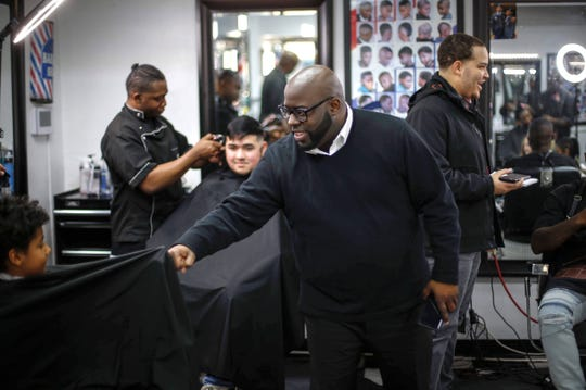 The Rev. Rob Johnson chats with staff and patrons after getting his hair cut by Daniel Bradshaw Jr. at Platinum Kutz in Des Moines.