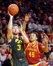 Iowa guard Jordan Bohannon shoots as Iowa State guard Rasir Bolton depends as the Hawkeyes take on the Cyclones at Hilton Coliseum in Ames Thursday, Dec. 12, 2019.