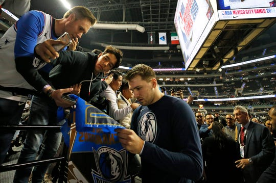 Mavs' Luka Doncic signs autographs for fans prior to the game against the Pistons in Mexico City, Thursday.