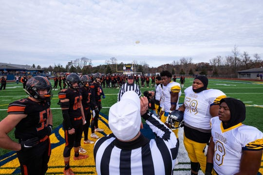 Players watch the coin toss at the start of the MHSAA Division 5 state semifinal between Almont and Detroit Denby Saturday at Walled Lake Central.  photos by Brian Wells/Times Herald Players watch the coin toss at the start of the MHSAA Division 5 state semifinal between Almont and Detroit Denby Saturday, Nov. 23, 2019, at Walled Lake Central.