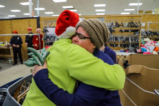 Yolanda Cruz, 49, of Lincoln Park gets a hug from a Secret Santa after accepting $100 from them while working at Salvation Army  in Lincoln Park, Mich. on Thursday, Dec. 12, 2019.