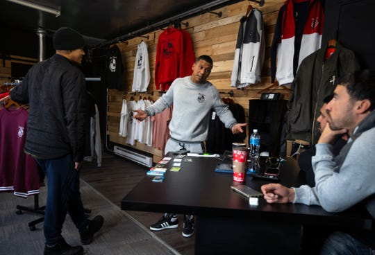 Jose Rivera (center) talks with others in his clothing store Detroit Forever 313 on Michigan Ave. on Friday, December 13, 2019. Rivera started his clothing line following his release from prison after he began sketching clothing logos while he was incarcerated.