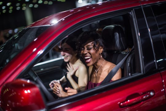 Devon Williams (right) of Sterling Heights, Arda Kafafian (left) of Birmingham and Ebony Flake (background) of Detroit dance in a Jeep Cherokee Track Hawk during the 2019 North American International Auto Show Charity Preview at Cobo Center in Detroit on Friday, January 18, 2019.