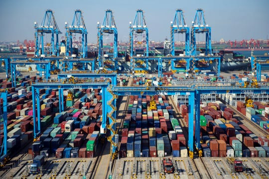 In this Thursday, Nov. 28, 2019, photo, trucks load containers at the automated container dockyard in Qingdao in east China's Shandong province.