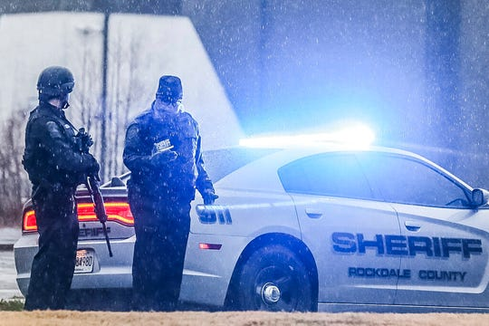 Authorities stand outside a business in Conyers, Ga. on Friday, Dec. 13, 2019. Dart Container Corp. spokeswoman Margo Burrage says a person entered the company's Conyers plant around 7 a.m. with a gun.