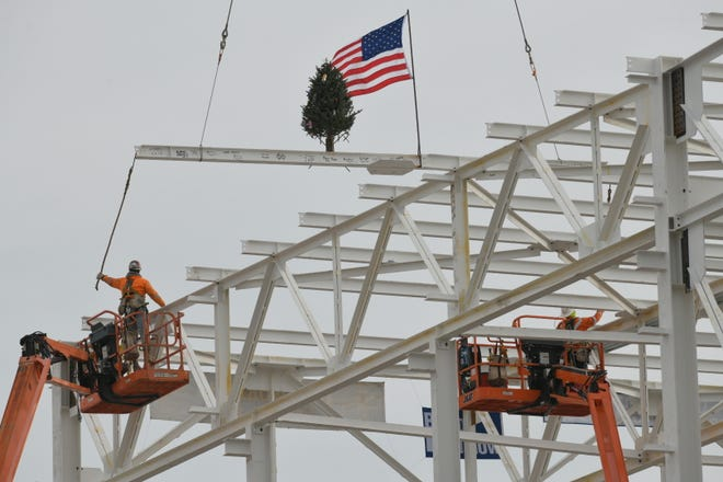 Construction workers get ready to position and install the final beam of structural steel as it is lowered by crane to the roof of the paint shop at FCA's Mack Avenue plant in Detroit four months to the day since the first beam was placed on the project.