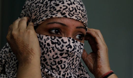 In this Thursday, Oct. 31, 2019, photo, Amandeep Kaur, a former tramadol user, covers her face at the de-addiction at center in Kapurthala, in the northern Indian state of Punjab.